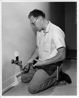 Photograph of an unidentified person installing a phone jack