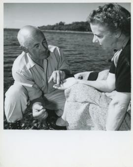 Photograph of Edith and Thomas Head Raddall discussing ancient arrowheads found at the Indian Gar...