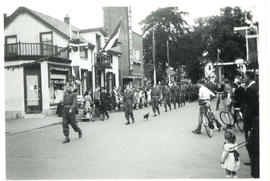 Photograph of a parade of Canadian Armed Forces marching down a street in Holland