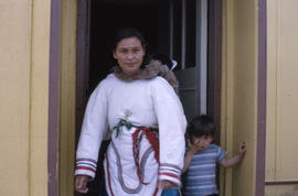 Photograph of Joanna Koneak standing in a doorway with two children