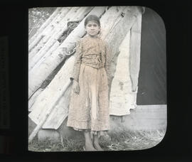 Photograph of unidentified Mi'kmaq girl standing in front of wigwam