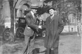 Photograph of A. S. MacKenzie shaking hands with an unidentified man