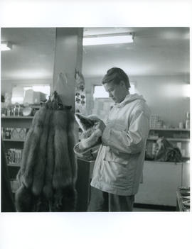 Photograph of Barbara Hinds looking at fur slippers in a store