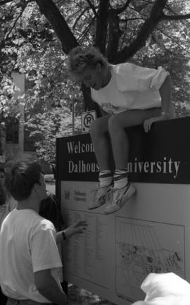 Photograph of a student on the Dalhousie welcome sign