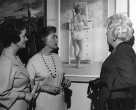 Photograph of three unidentified women looking at a painting