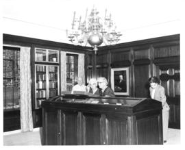 Photograph of people looking at a display case in the Kipling room at the Macdonald library