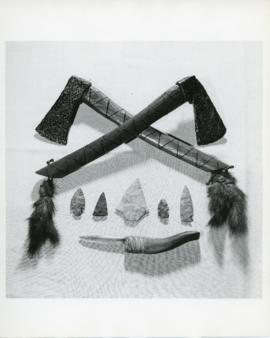 Photograph of two iron hatchets or tomahawks decorated with feathers, five stone arrowheads, and ...