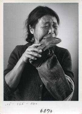 Photograph of a woman chewing sealskin boots in Cape Dorset, Northwest Territories