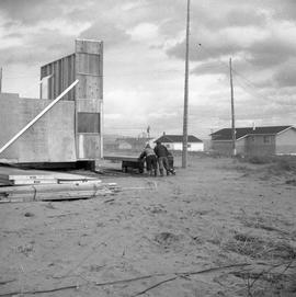 Photograph of three people moving a section of a house in Fort Chimo, Quebec