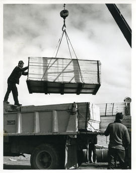 Photograph of a crate being loaded onto a truck with a crane