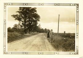 Photograph of two women standing on the side of the road along Hospital Wood, looking north towar...