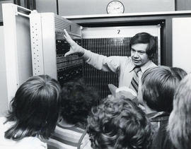 Photograph of a man giving a tour of the Dalhousie Computer Centre to a group of children